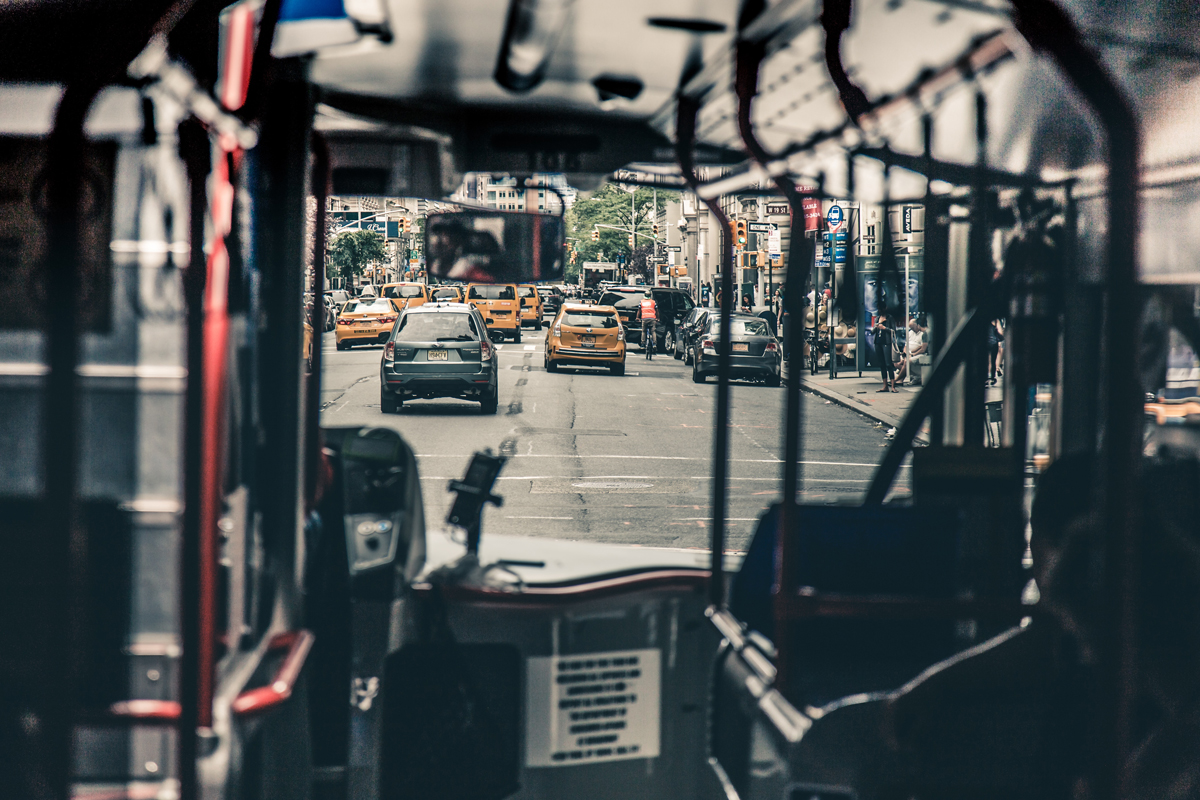 Inside a NYC bus with a view of cars and taxis