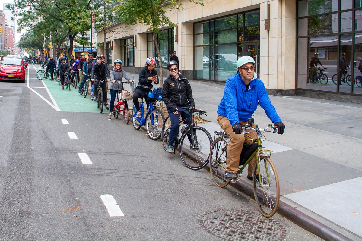 A line of cyclists bike down a bike lane