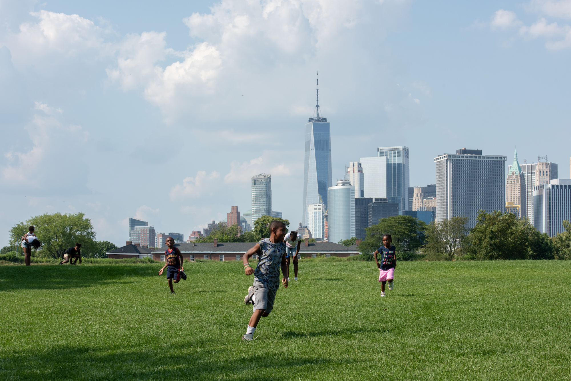 people running in park with city skyline in the background