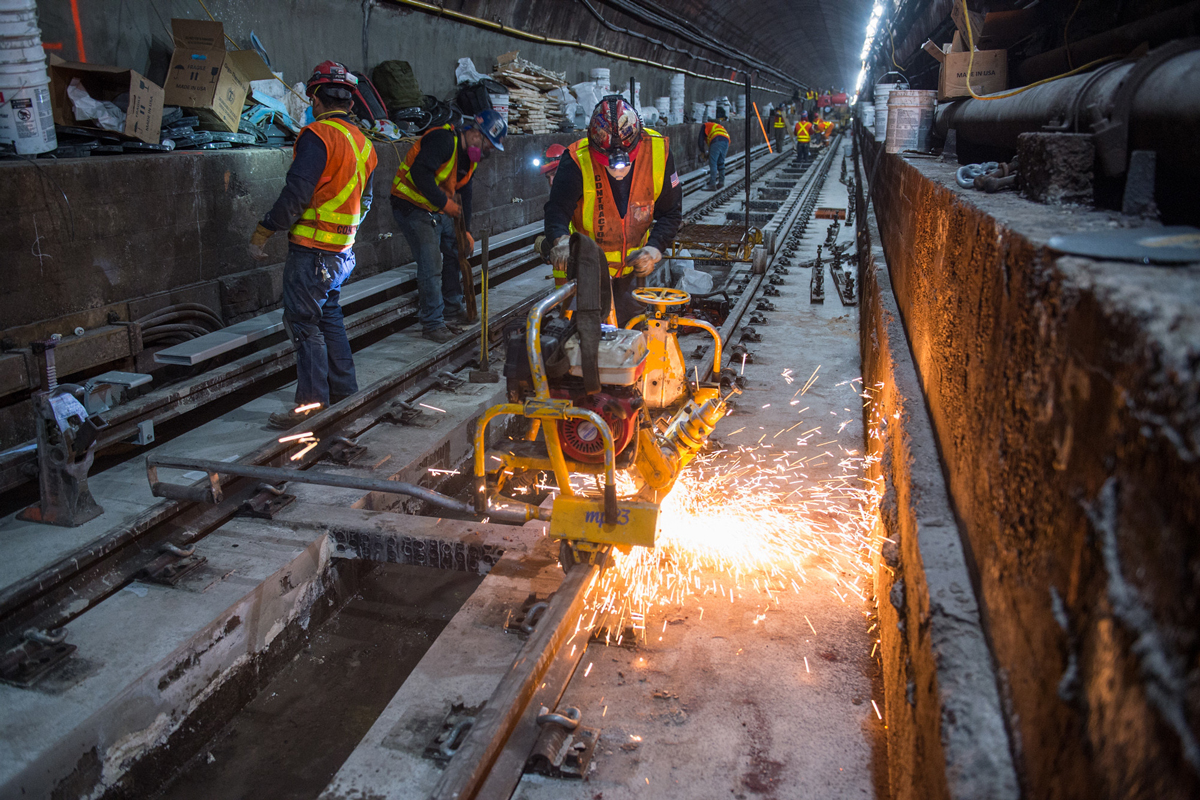 Construction workers making repairs to steel work in large underground subway tunnel
