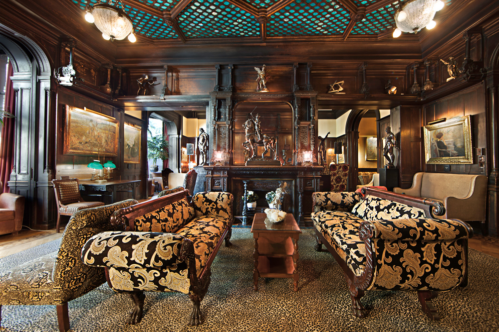 A living room with two patterned couches and many small bronze statues on shelves