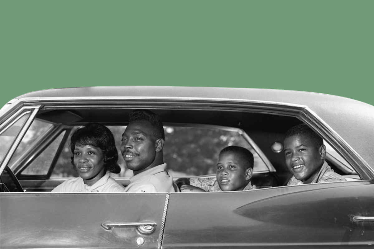 A black and white photo of a family driving in a car