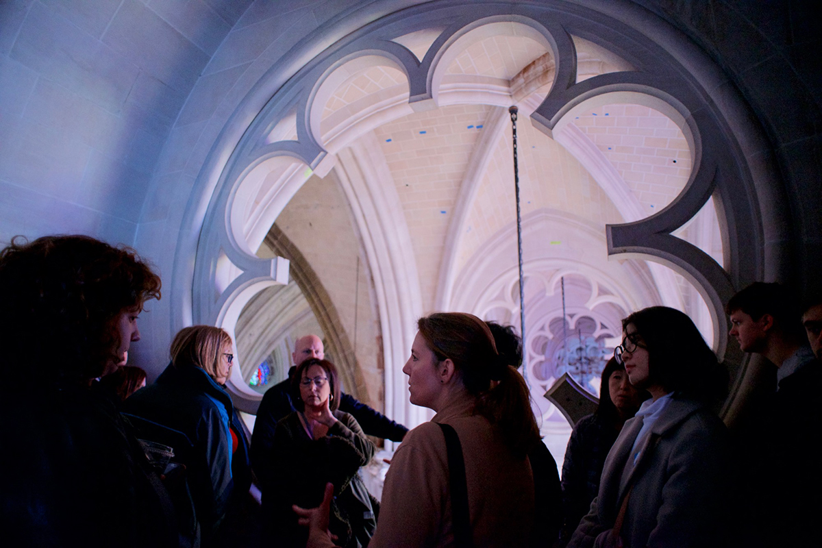 Visitors huddle by one of the large rosette windows above the cathedral