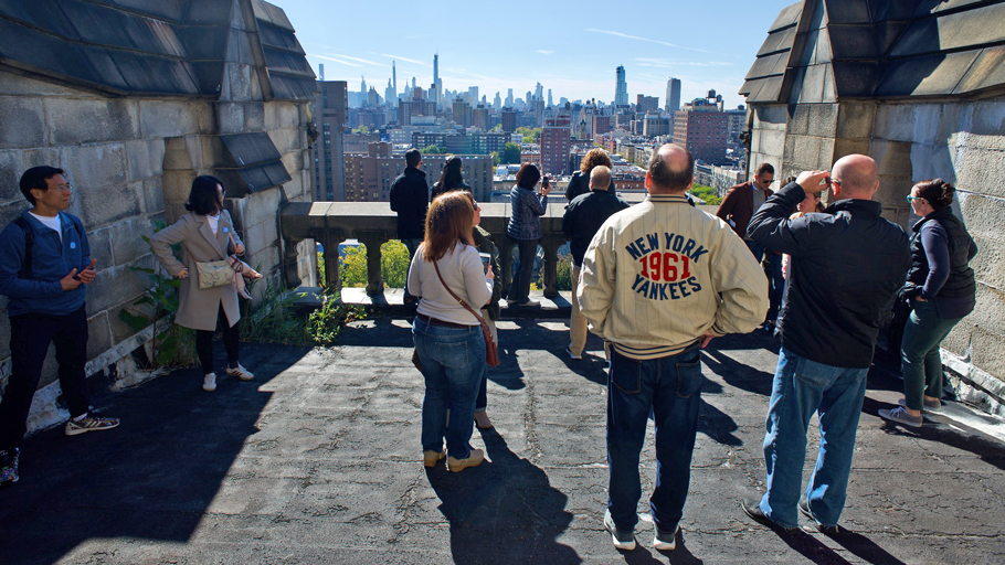 Visitors on a rooftop with views of the New York skyline