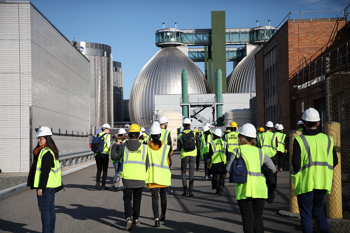 Visitors in hardhats walk through a plant towards large digester eggs