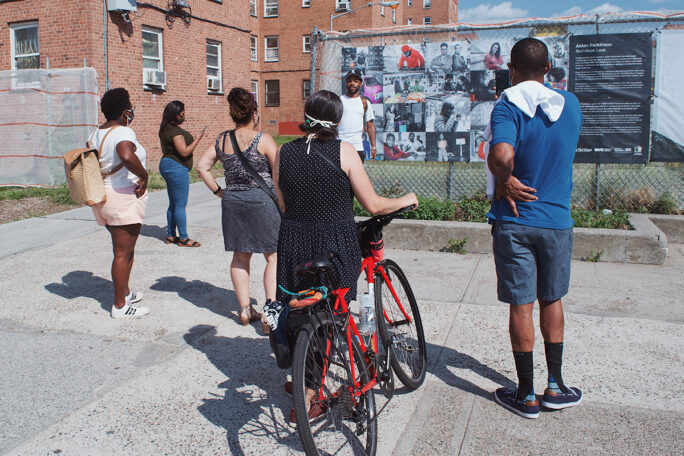 A group views an art installation of photographs on a fence at the Red Hook Houses.