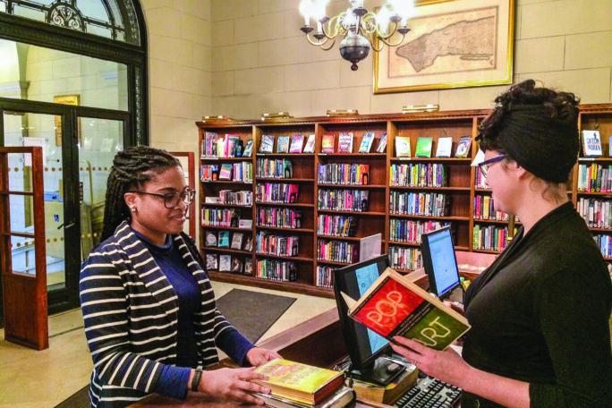A librarian checks out books to a reader