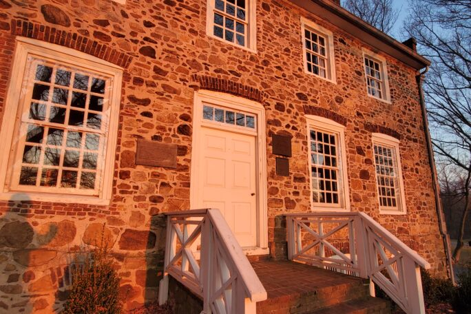 A two-story stone building with large white-framed windows and door.