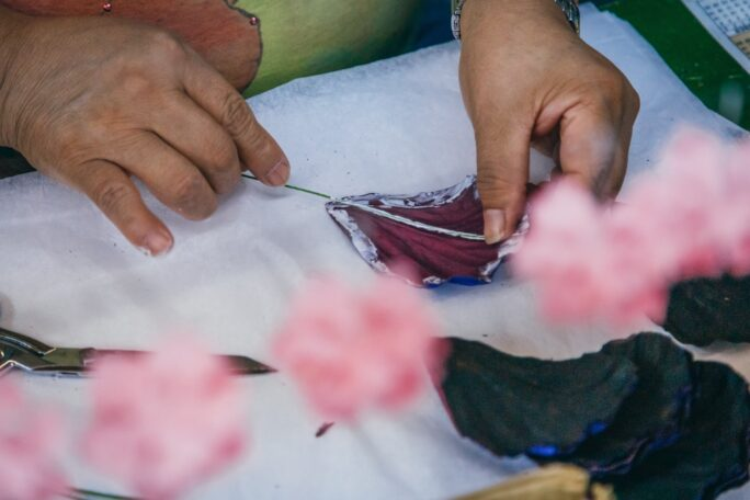 Close up of a pair of hands carefully working on a petal