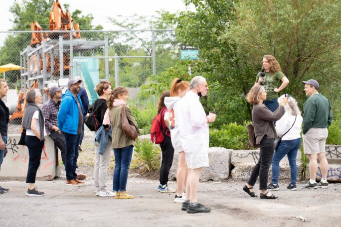 A group of people listing to a speaker on an industrial lot with plants in the background