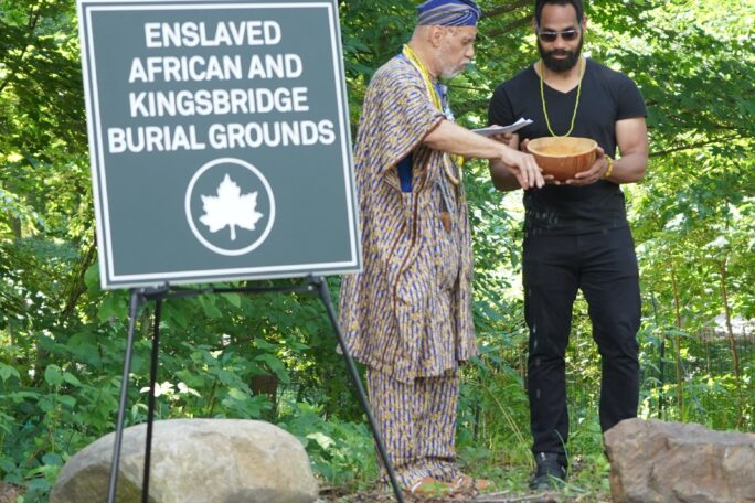 Chief Baba Niel Clarke dressed in traditional African clothing including a head wrap and beads stands next to a sign for the Enslaved African and Kingsbridge Burial Grounds.  He is sprinkling blessed spirits on the ground from a ceremonial bowl made from a gourd.