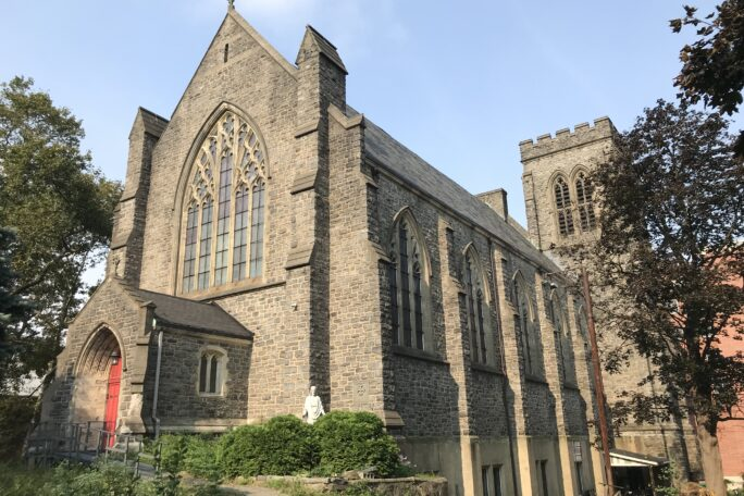 Neo-Gothic style stone church with stained glass windows and bell tower