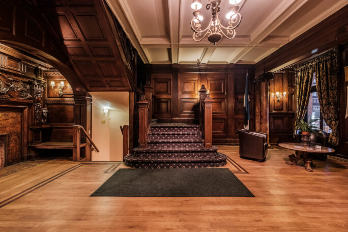 Interior of the Estonian House. Image features a carpeted staircase and a room with wood paneling