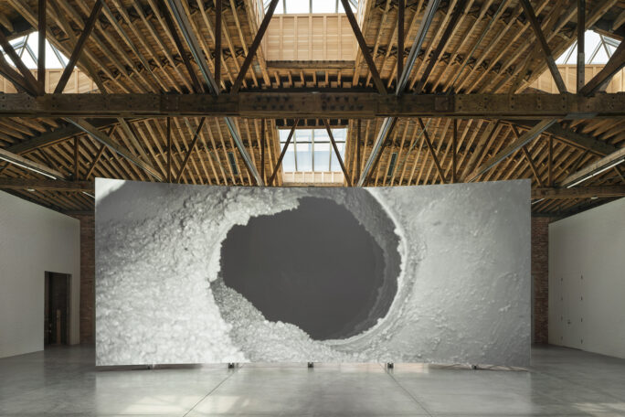 Lucy Raven's Ready Mix film on view below trussed ceiling and skylights at the revitalized Dia Chelsea galleries.