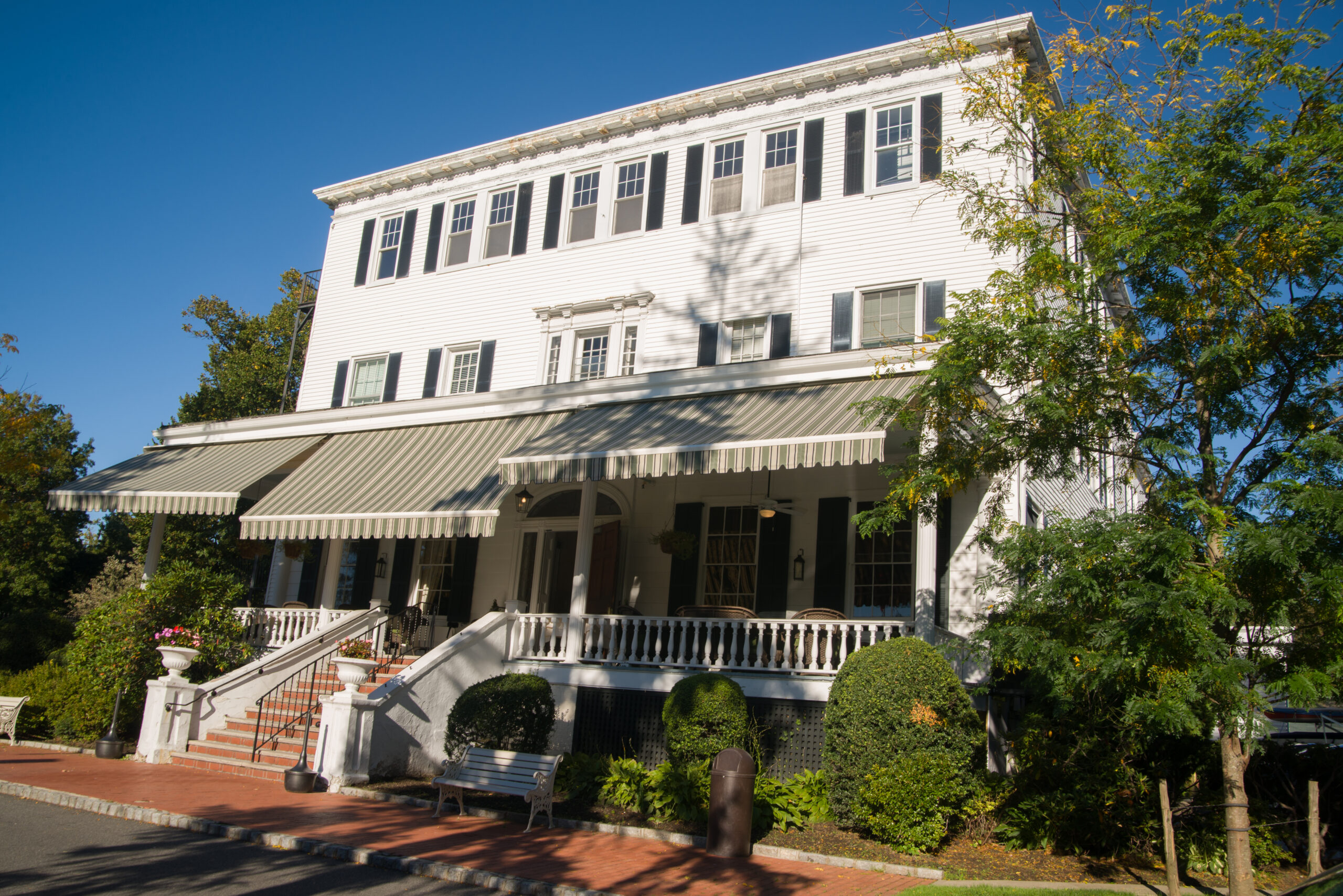 A three-story white wood home with green striped awnings over a large brick porch.