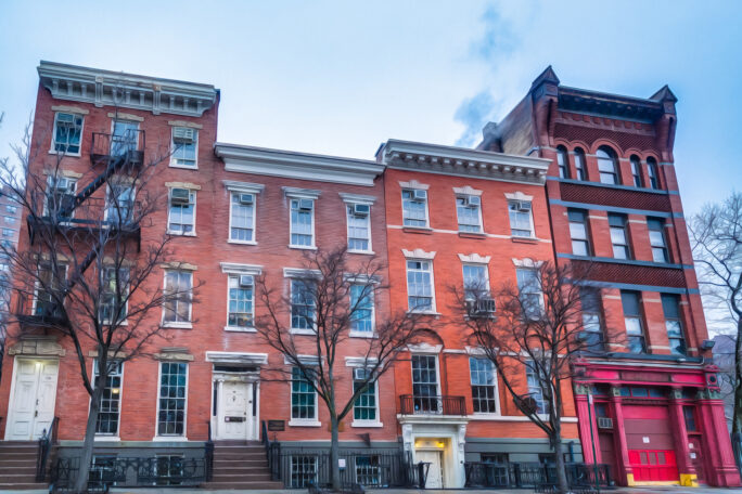Four brick rowhouses with different heights and facade detailing