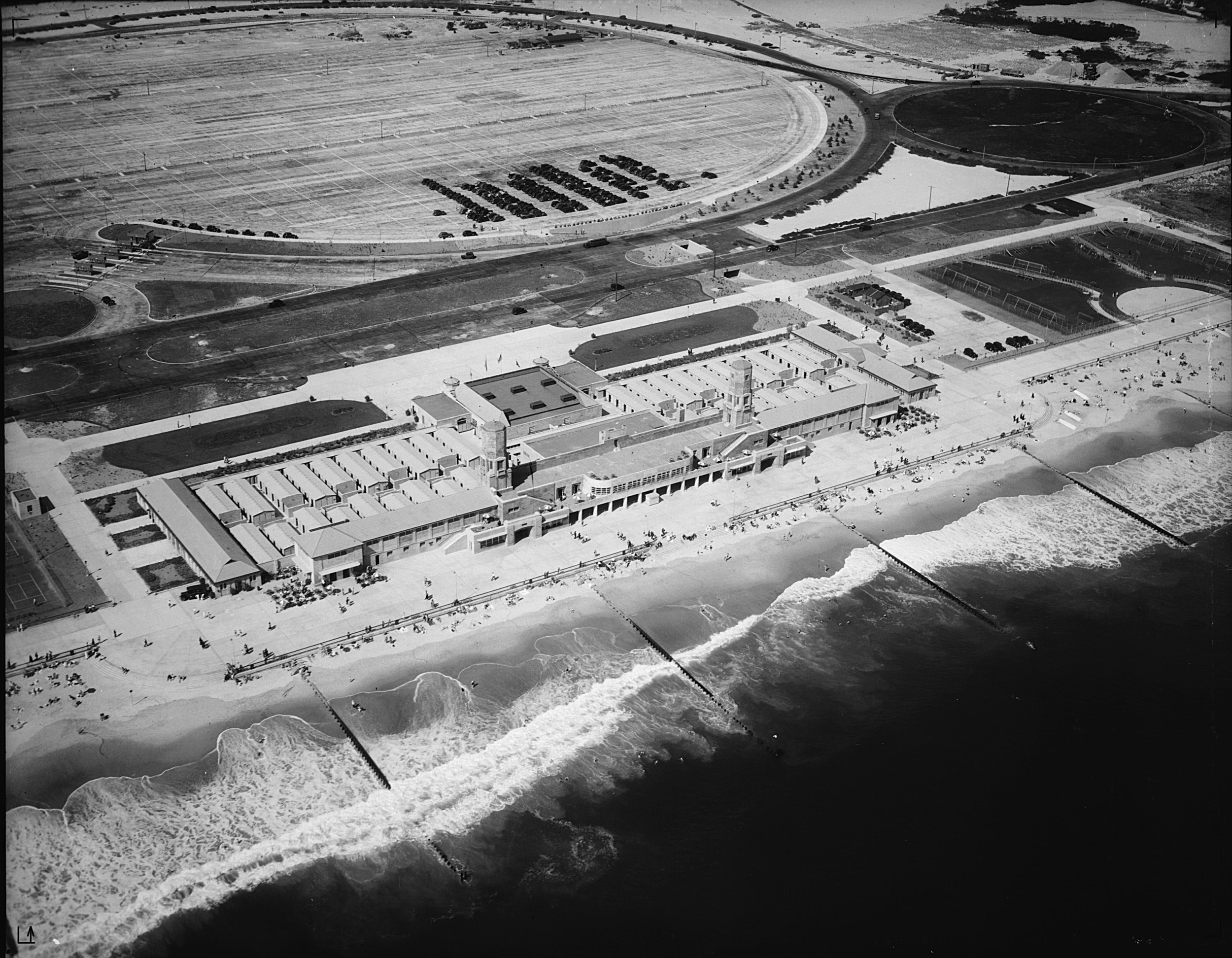 Black and white aerial photograph of a large Art Deco style bathhouse complex and boardwalk with the ocean and piers adjacent