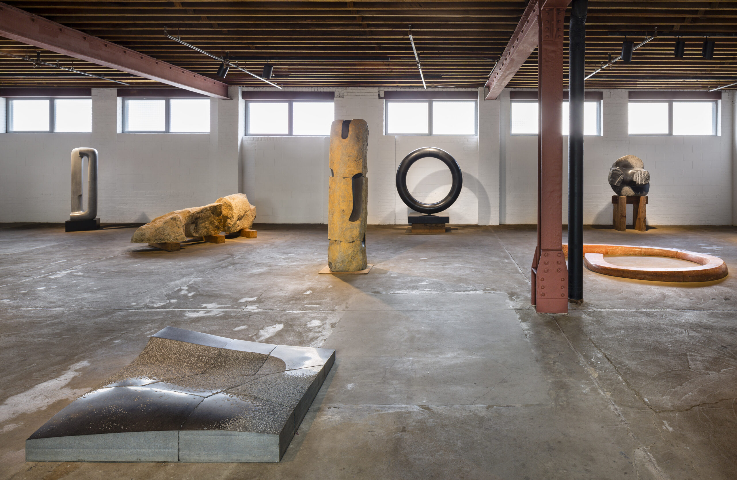 Interior industrial gallery space filled with stone sculptures in geometric and organic shapes.