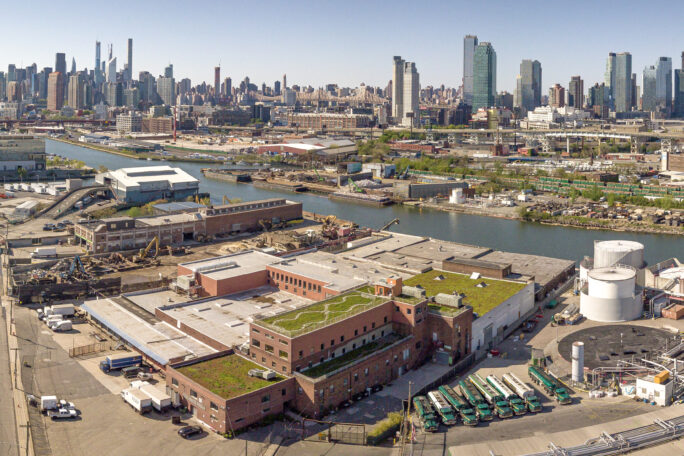 Image of a large building with vegetated roof tops surrounded by heavy industrial operations with Newtown Creek
