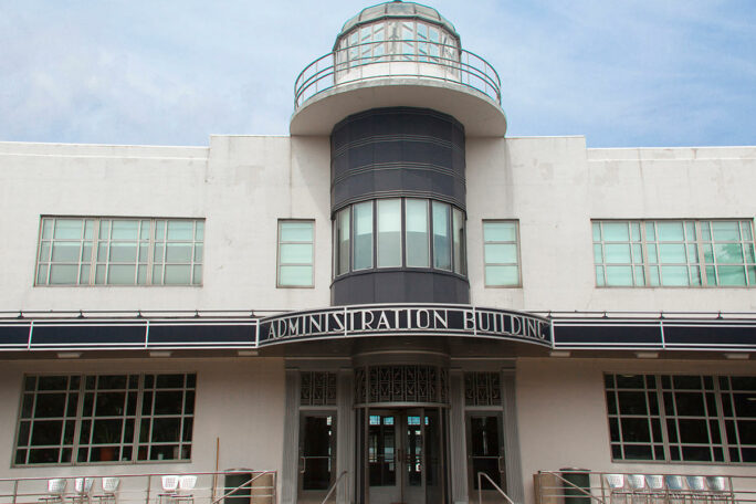 Art deco two story building with a glass cupola over a center tower and marquee reading Administration Building