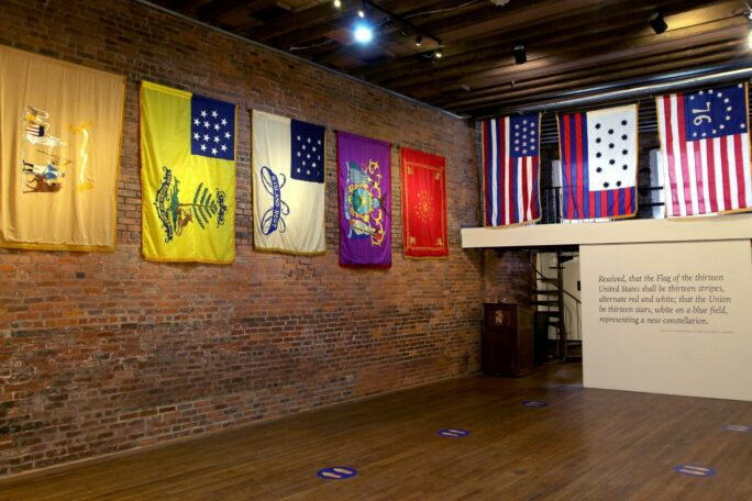 """A Fraunces Tavern Museum gallery filled with flags of various colors. Text in the corner reads """"Fraunces Tavern Museum Guided Tours."""""""
