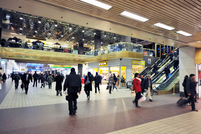 Hallway in the Terminal with many commuters and a cafe.