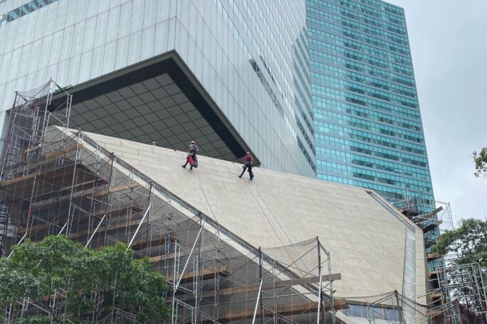Workers on the sloped concrete roof of the church