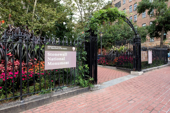 A black fence with the sign reading 'Stonewall National Monument' and an archway into Christopher Park