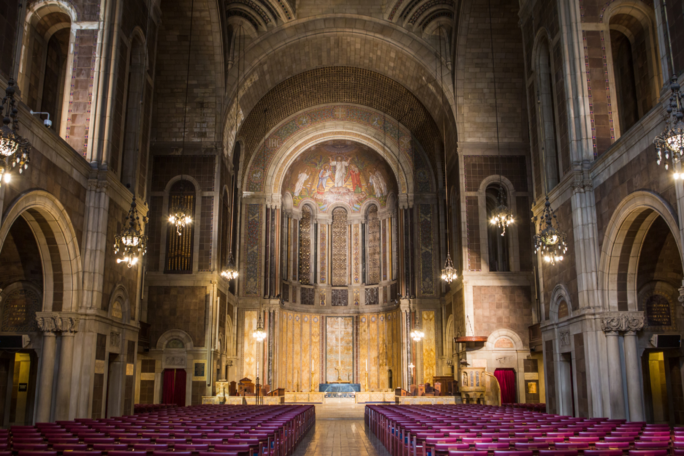 Image of a church interior with a dramatic central arch and many rows of red chairs