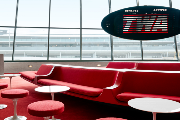 Lounge in the TWA Hotel with red couches and a TWA signboard