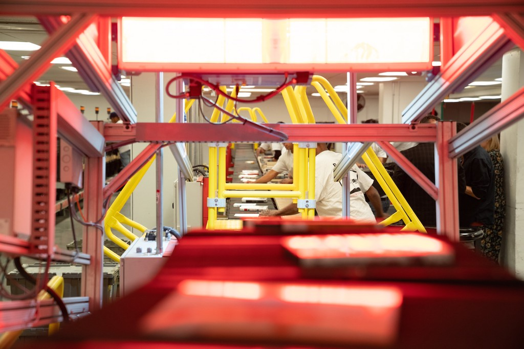 Red conveyer belt with books on it headed toward book sorters