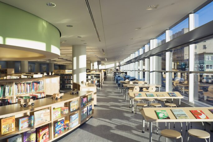 Library interior with tables next to a row of windows and an undulating shelf