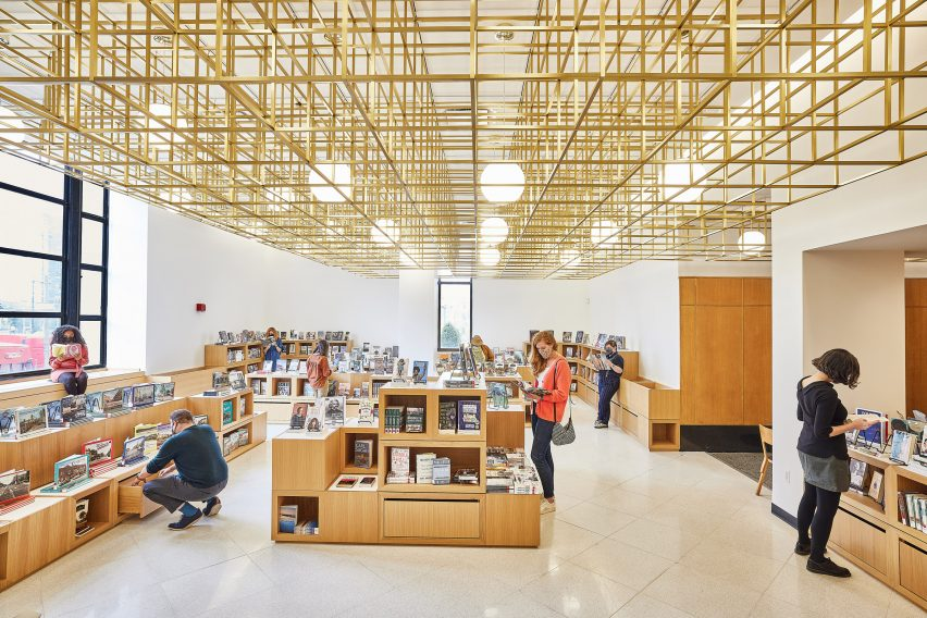 Library interior with low bookshelves and large gold metal light fixture