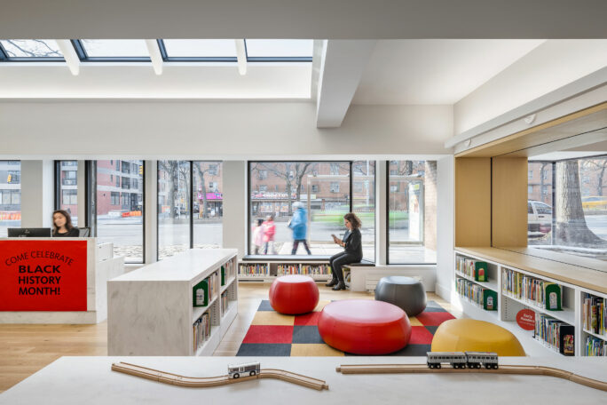 A library interior with skylights and large windows at street level.