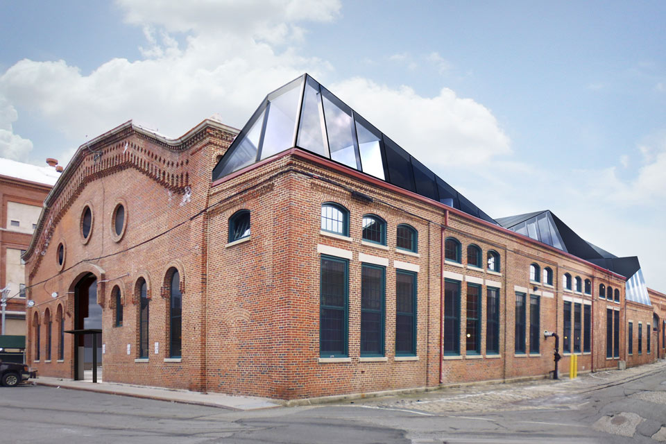 Brick warehouse with modern glass roof extending above it on one side.