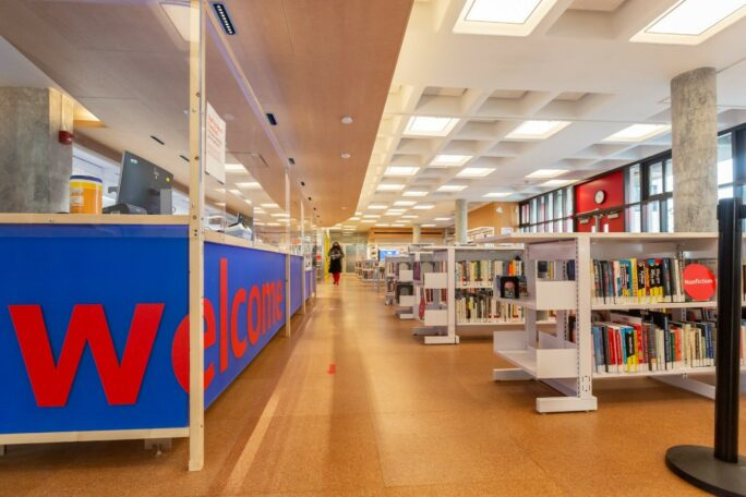 Library interior with long blue welcome sign