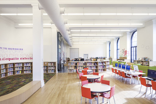 A childrens' library room with colorful chairs and low bookshelves