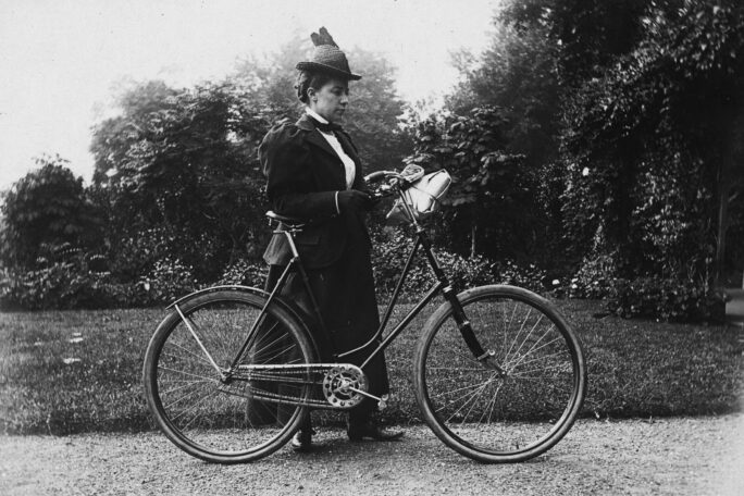 black and white photo of woman with bicycle